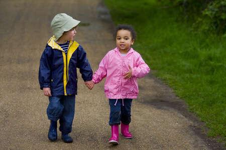 country park: Un peque�os muchacho y muchacha que usan Wellington patea llevar a cabo las manos y caminar a trav�s de un parque del pa�s Foto de archivo