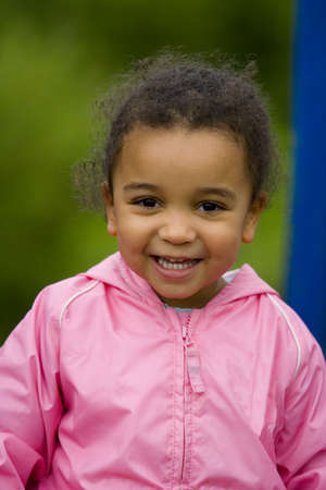 A beautiful mixed race girl dressed in pink and smiling Stock Photo