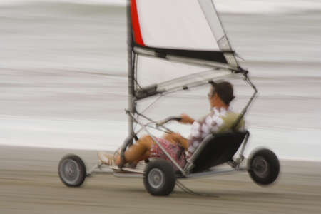 Motion blurred shot of a land yacht speeding down a beach photo