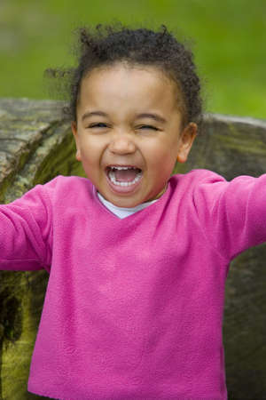 loudly: A beautiful mixed race girl sitting on a log and laughing - very loudly