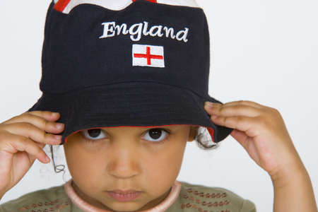 A young mixed race girl pulling on an England hat photo