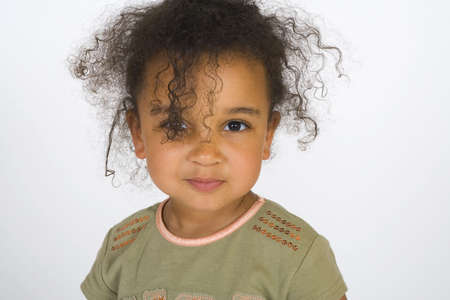 A beautiful mixed race girl with curly hair and a smiley face.