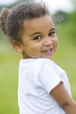 Una muchacha mezclada hermosa de la raza mira detr�s sobre su hombro Foto de archivo
