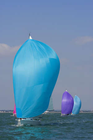Yachts racing with coloured spinnakers raised