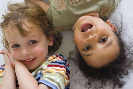 mixed race: Un muchacho rubio joven y muchacha de la raza mezclada hermosa una peque�a que r�en para la c�mara fotogr�fica Foto de archivo