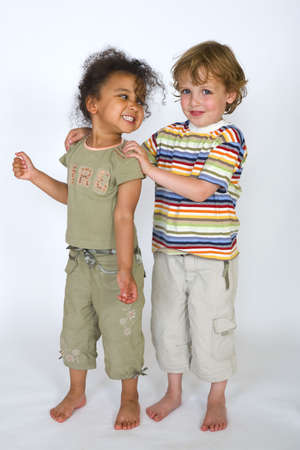 A beautiful mixed race girl and a blonde boy stand together laughing