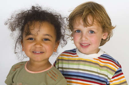 A beautiful mixed race girl and a blonde boy stand together