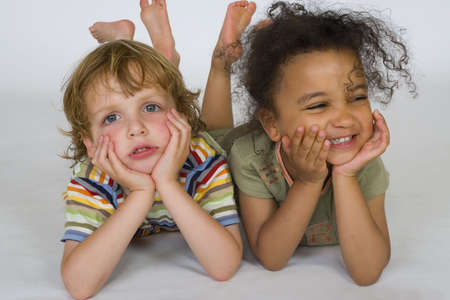 mixed race: Una hermosa ni�a de raza mixta y de un chico rubio jugando juntos, uno feliz, uno triste