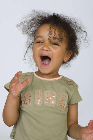 mixed race: Una hermosa ni�a de raza mixta cantando con alegr�a.  Foto de archivo