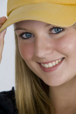 A pretty girl with bright blue eyes and blonde hair and wearing a baseball cap. photo