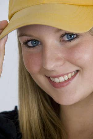 bionda occhi azzurri: Una ragazza graziosa con gli occhi ed i capelli del blonde e luso blu luminosi della protezione di baseball. Archivio Fotografico