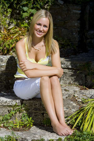 A beautiful young blond woman with a big gorgeous smile and bright blue eyes sitting in summer sunshine. Stock Photo - 509307