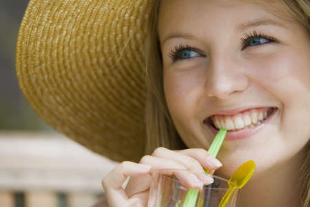A beautiful young blond woman enjoying a tall drink  and wearing a big straw hat. Stock Photo