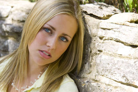 sultry: A beautiful young woman with bright blue eyes and blonde hair rests against a stone wall