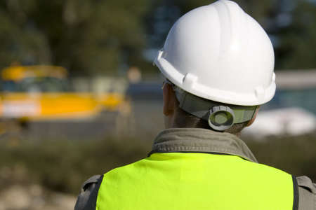 construction hat: A construction worker on site and dressed in safety clothing