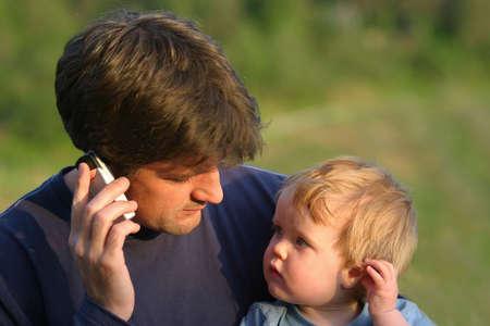 telecoms: Un giovane figlio imita il padre, che sta parlando sul suo cellulare  Archivio Fotografico