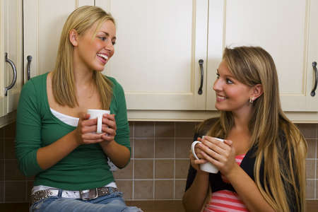 rumours: Two beautiful young women drinking and chatting in the kitchen. Stock Photo