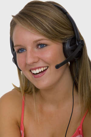 telephonist: A beautiful young blonde telephonist smiling and speaking on a headset