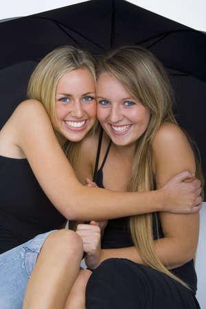 amigos abrazandose: Dos bellas mujeres j�venes cuddling juntos bajo un gran paraguas negro