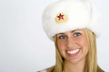 russian hat: A beautiful young Russian girl smiling and wearing a fur hat and shot in studio conditions