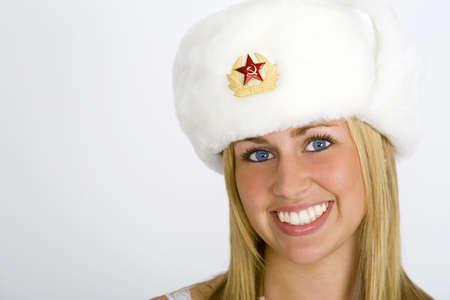blonde yeux bleus: Une belle jeune fille russe souriant et portant un chapeau de fourrure et tourn� dans des conditions de studio