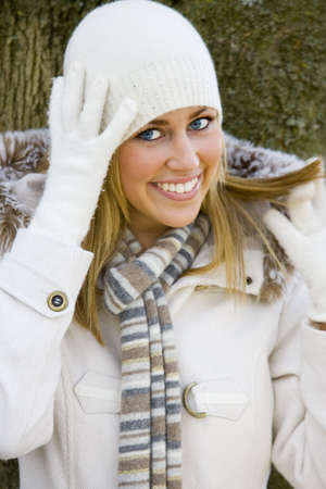 A beautiful blue eyed young woman wearing white winter clothes and smiling Stock Photo