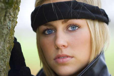 A beautiful blue eyed young woman wearing a black headband.