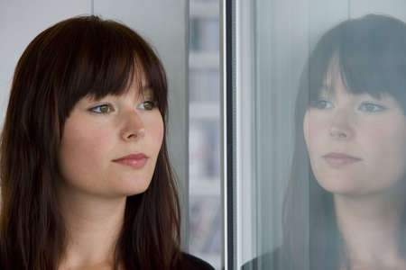 A beautiful young woman stares wistfully into a window where her reflection looks back at her. photo