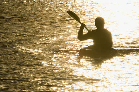 canoeist: A kayaker paddles across a lake illuminated by the setting sun. Stock Photo