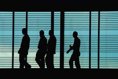 tradeshow: Silhouettes of workersexecutives in front of a hi tech background Stock Photo