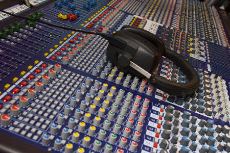 Close up of an audio visual mixing desk complete with headphones photo