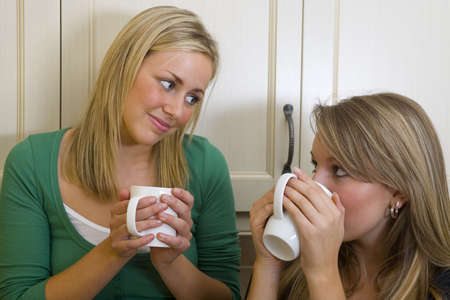 Two beautiful young women chatting over a warm drink. photo