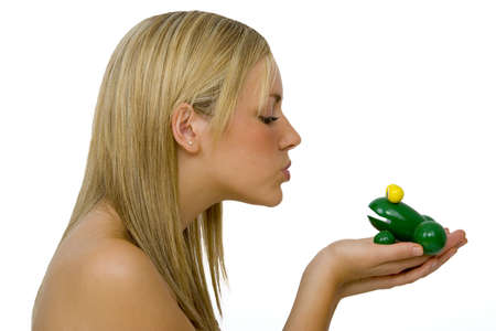 prince charming: A gorgeous young blond woman kissing a toy frog Stock Photo