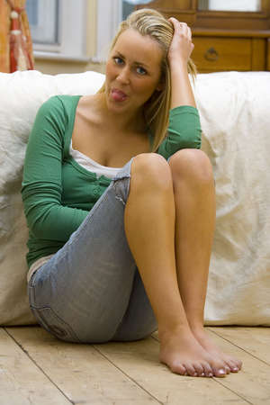 sexy blond: A sexy, gorgeous young blond woman with a cheeky smile sticking her tongue out and leaning against a bed