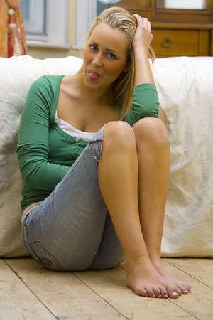 sexy f�sse: Ein sexy, wundersch�nen blonden jungen Frau mit einem frechen L�cheln h�lt ihre Zunge heraus und lehnt gegen ein Bett