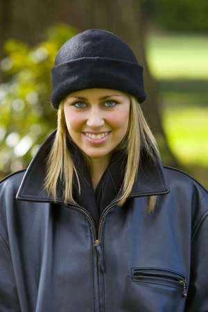beanie: A beautiful young blonde woman in a black beanie hat and leather jacket smiles enigmatically while backlit by autumnal sunshine
