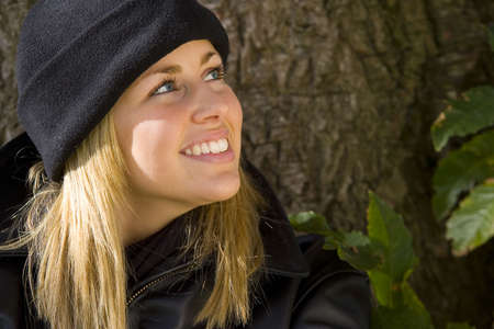 beanie: A beautiful young blonde woman in a black beanie hat and leather jacket smiles while leaning against a tree