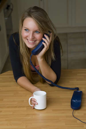 A beautiful young woman chatting happily on the phone and drinking a cup of teacoffee photo