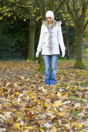 A beautiful young woman looking sad and standing alone in a leaf filled wood. photo