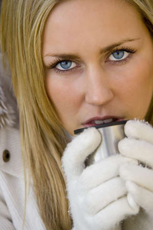 A stunningly beautiful blue eyed young woman keeping warm with a hot drink photo