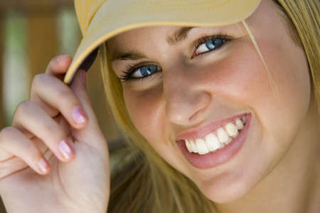 A beautiful young lady with blonde hair and blue eyes tips her baseball cap to the camera while bathed in sunshine. photo