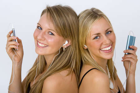 Two beautiful young women listening to their MP3 players photo