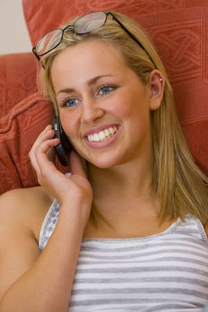 A beautiful blue eyed blond woman dressed smiling while calling on her mobile phone photo