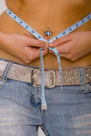 허리의 잘룩 한 선: Close up on a young woman with a pierced belly button measuring her waistline