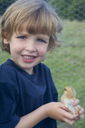 A young boy holds a little chick