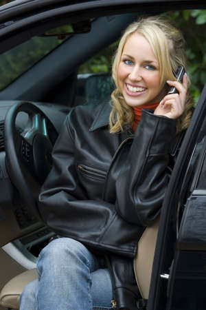 A beautiful young woman sitting in her expensive black 4 x 4 vehicle and talking on her mobile phone