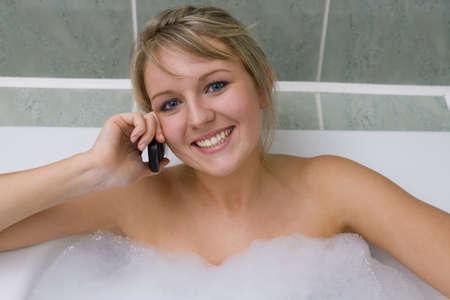 bionda occhi azzurri: Una bella ragazza di relax in una bolla bagno e chat sul proprio cellulare