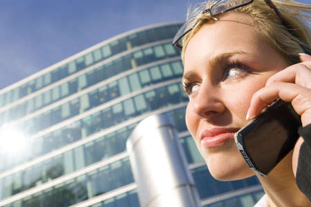 A beautiful young blonde female executive on her mobile phone in a hi tech landscape Stock Photo - 800545