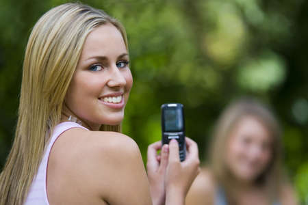 A beautiful young woman bathed in summer sunshine takes a picture of her friend using a mobile phone Stock Photo - 800553