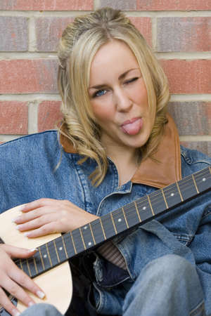 A beautiful young woman leaning on her guitar, winking and sticking out her tongue photo